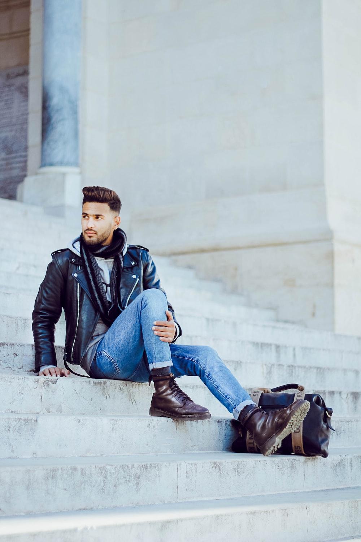 man wearing black leather jacket sitting on grey concrete stairs