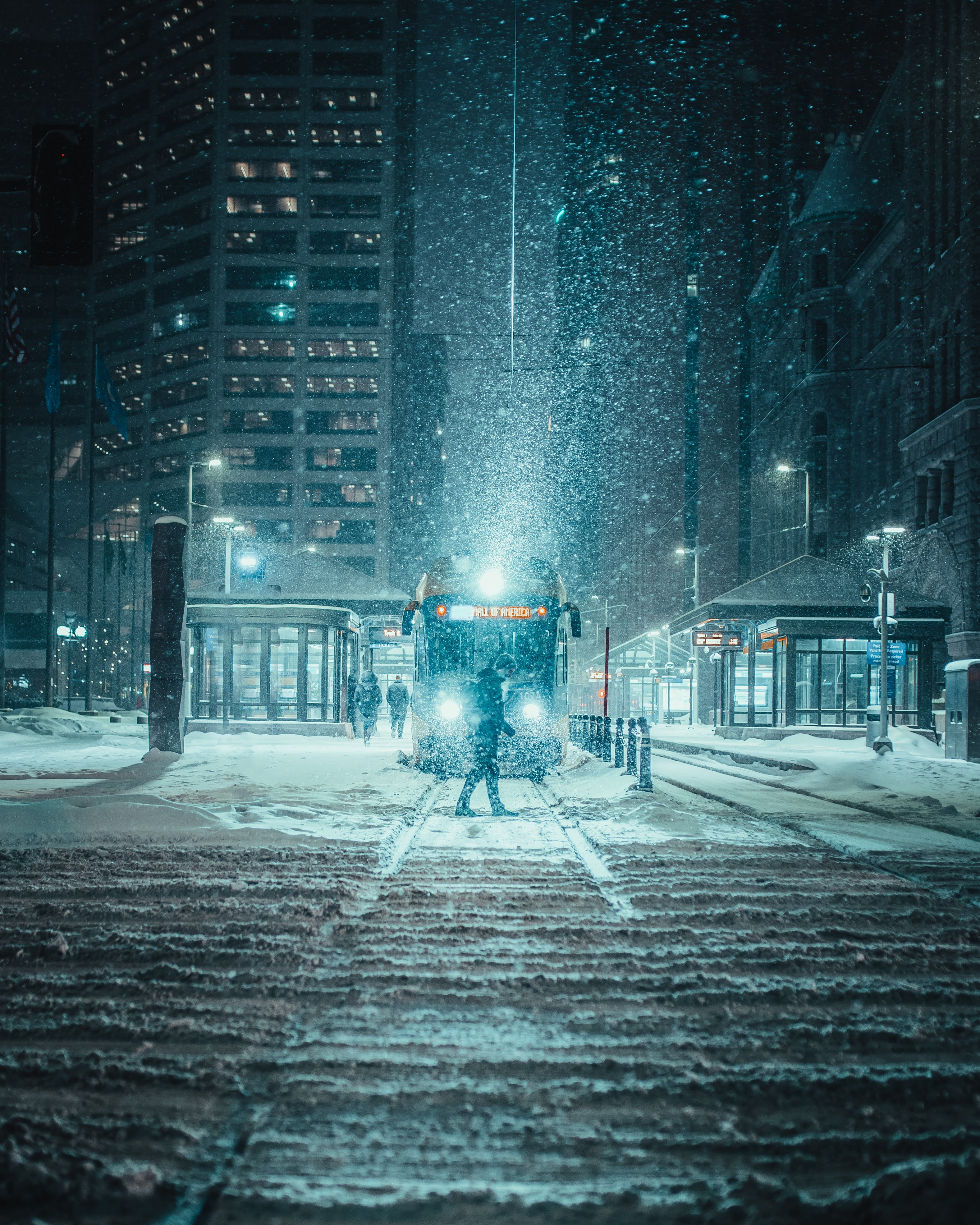 person standing on snow covered road during winter night