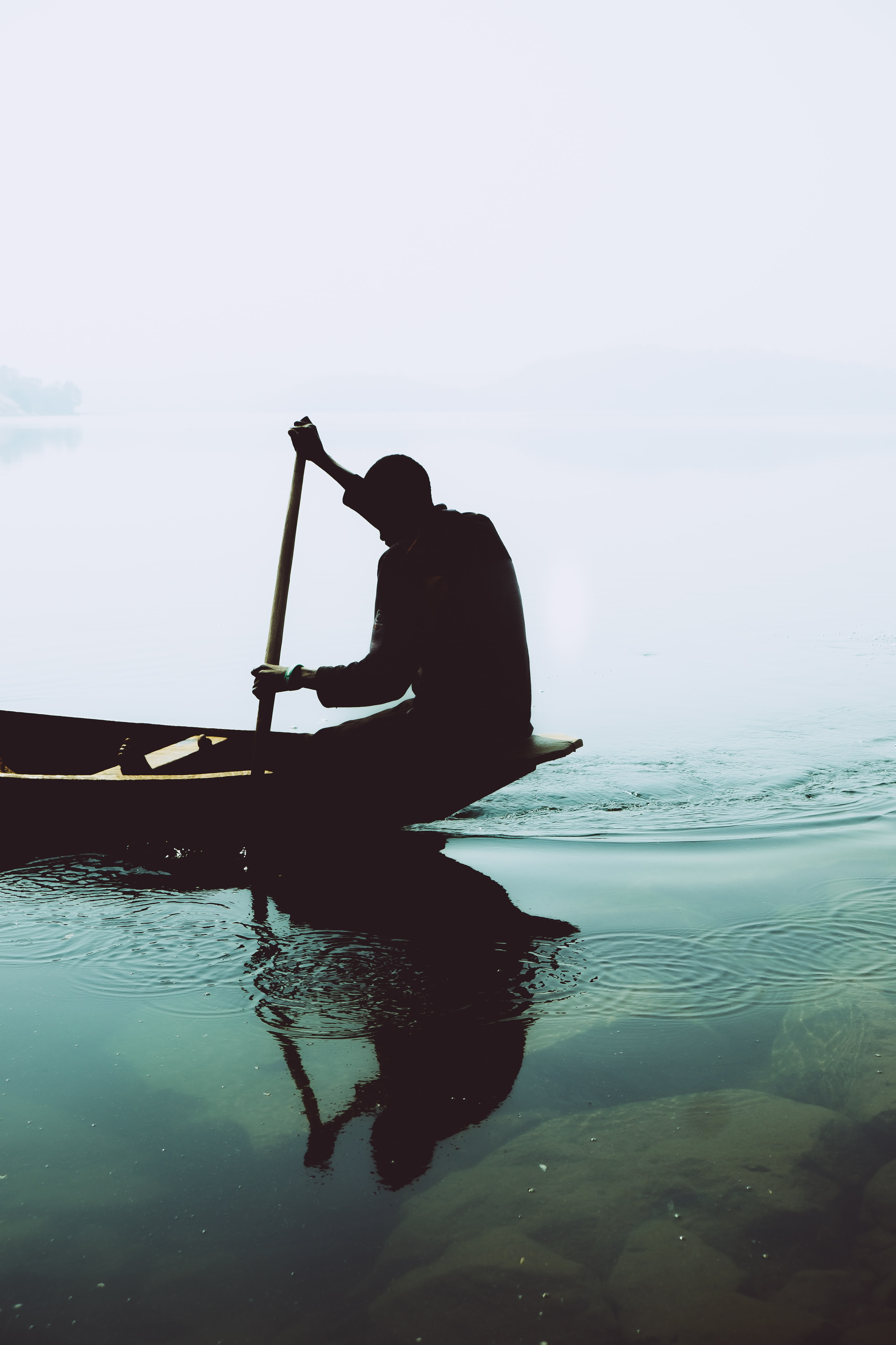 silhouette photography of person riding on jon boat
