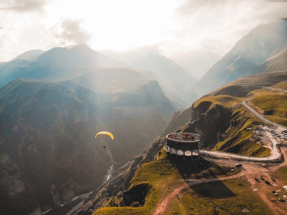 person paragliding on mountain cliff during daytime