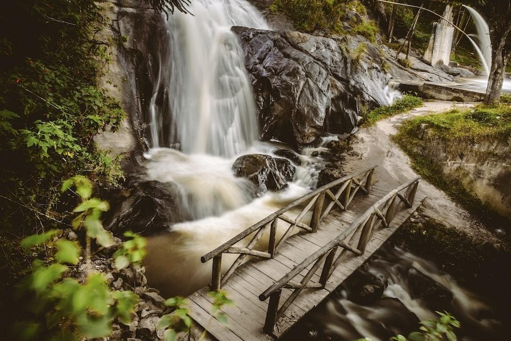 brown wooden bridge near waterfall