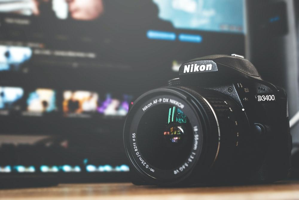 black and white Nikon D3400 DSLR camera on brown surface