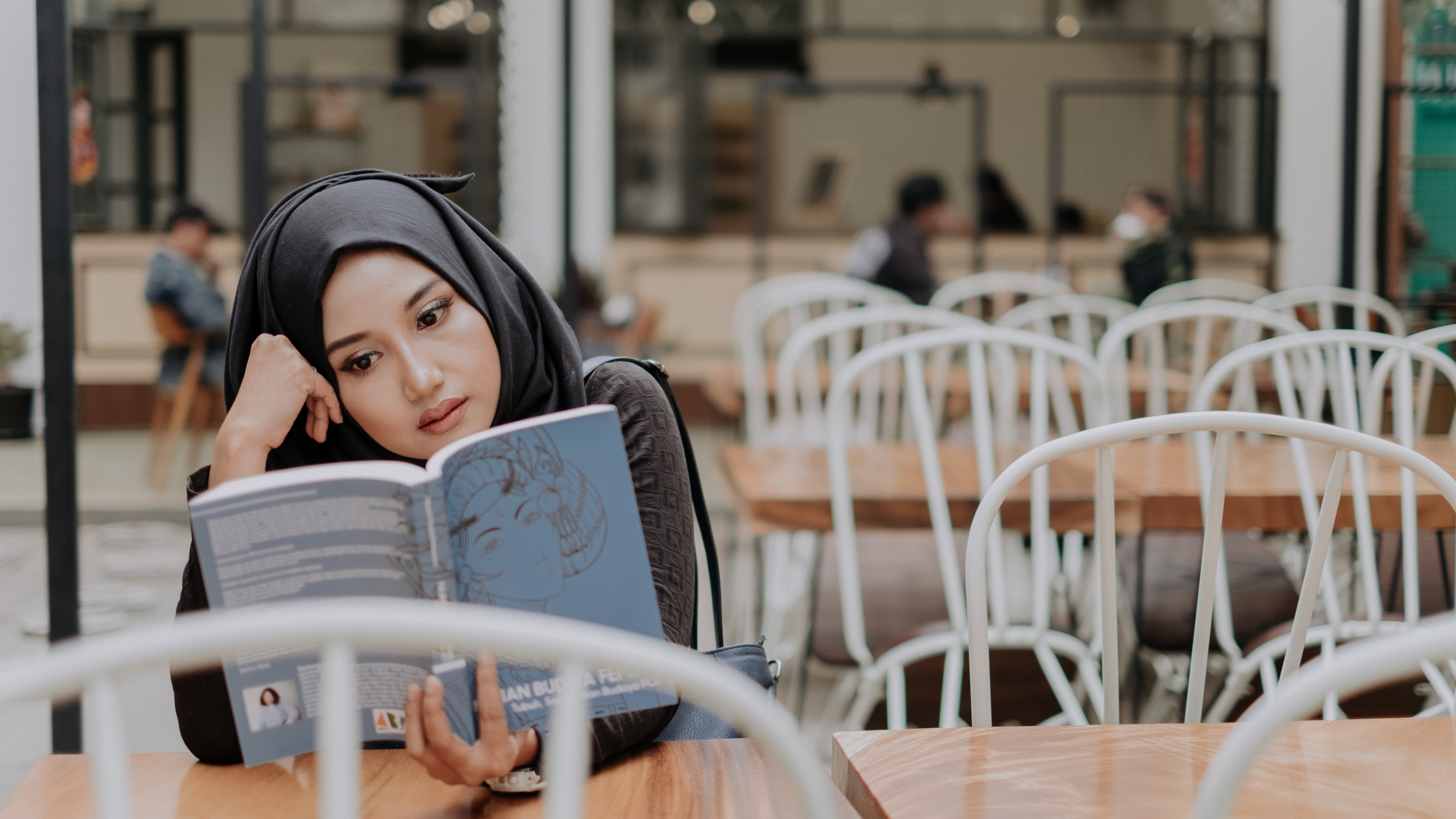 woman in black hijab reading book on selective focus photography