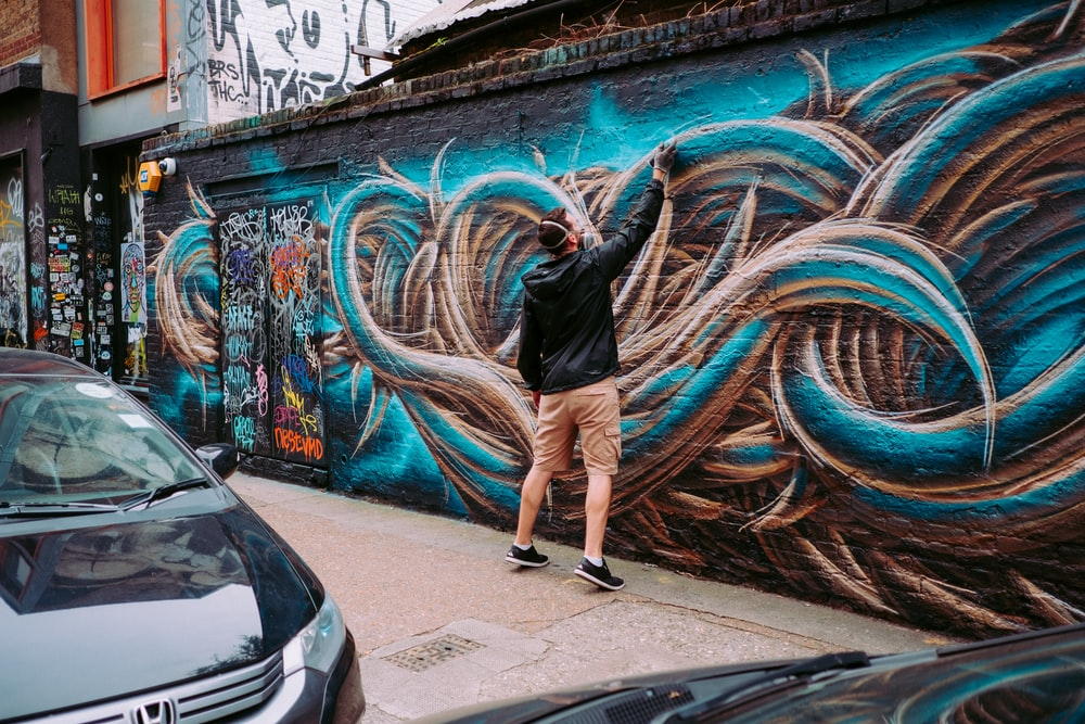 man painting on wall during daytime