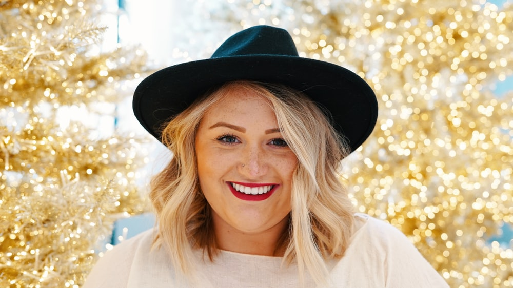 smiling woman wearing black fedora hat and white top