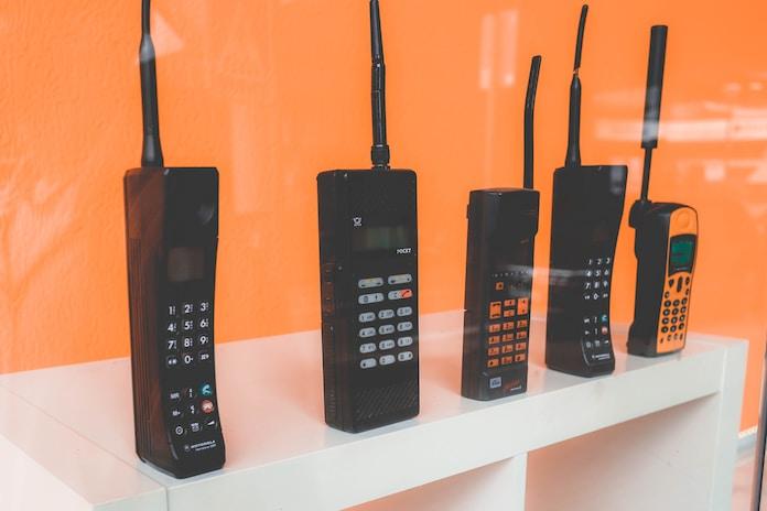 five assorted-brand wireless phones on desk