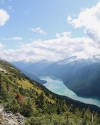 green grass mountain near lake during daytime