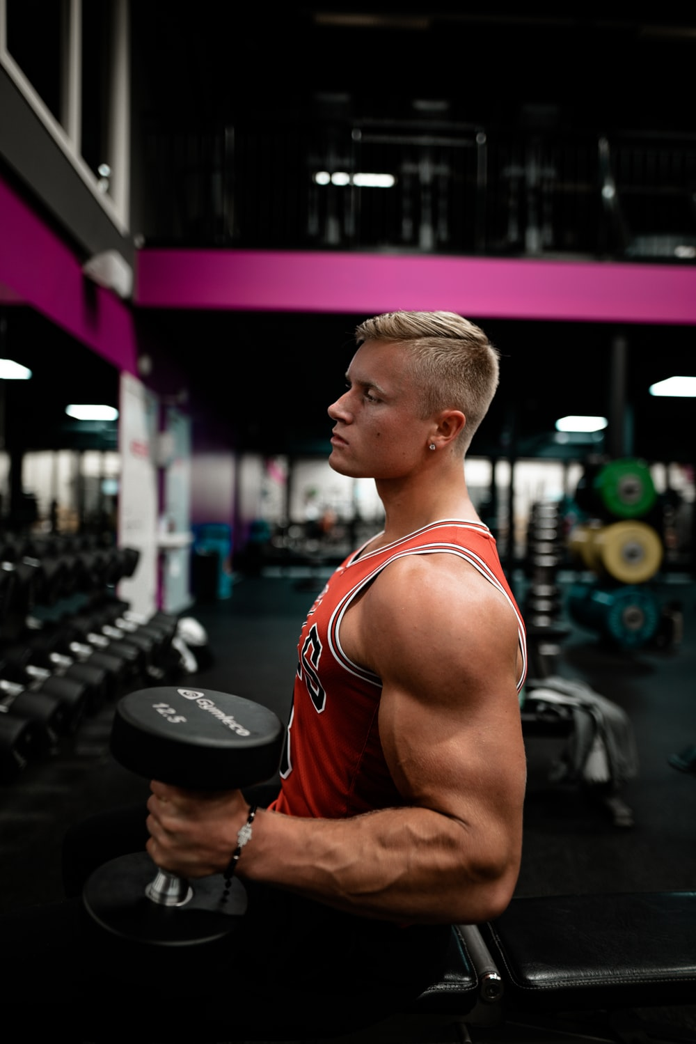 man standing while holding dumbbell inside gym