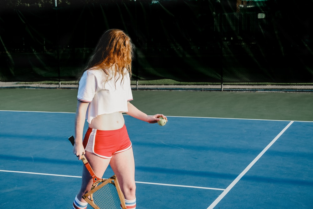 woman in white crop top and red and white dolphin shorts holding green ball and rocket