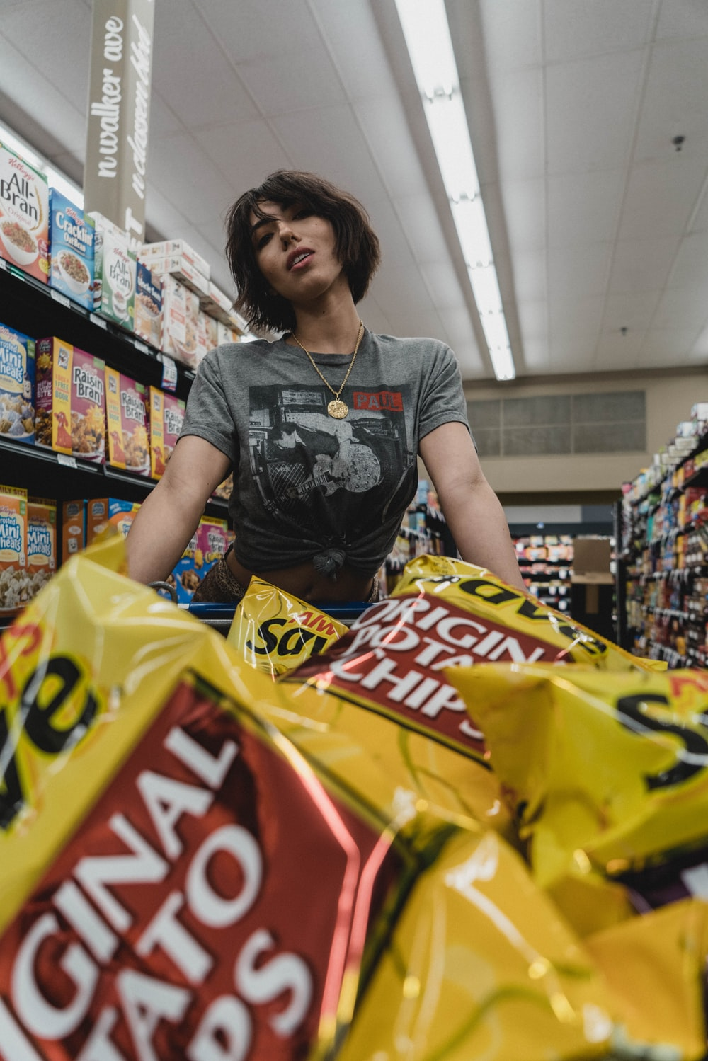 woman standing in front of chip bags inside store