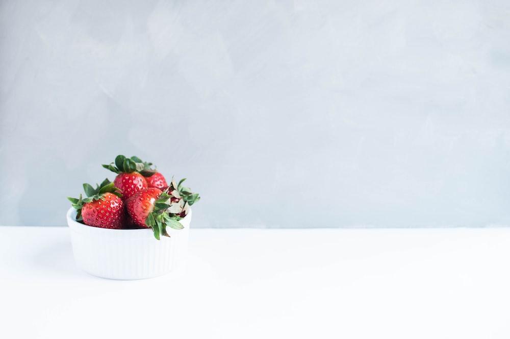 red strawberries on white round bowl