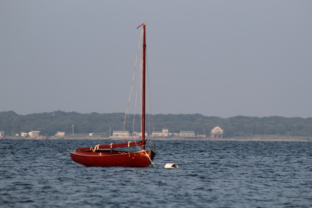 red wooden boat on sea during daytime