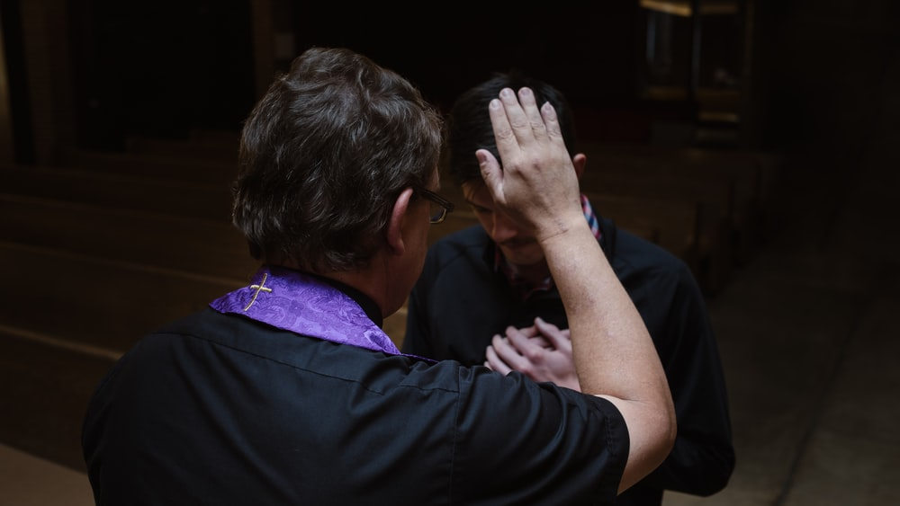 priest touching man's forehead