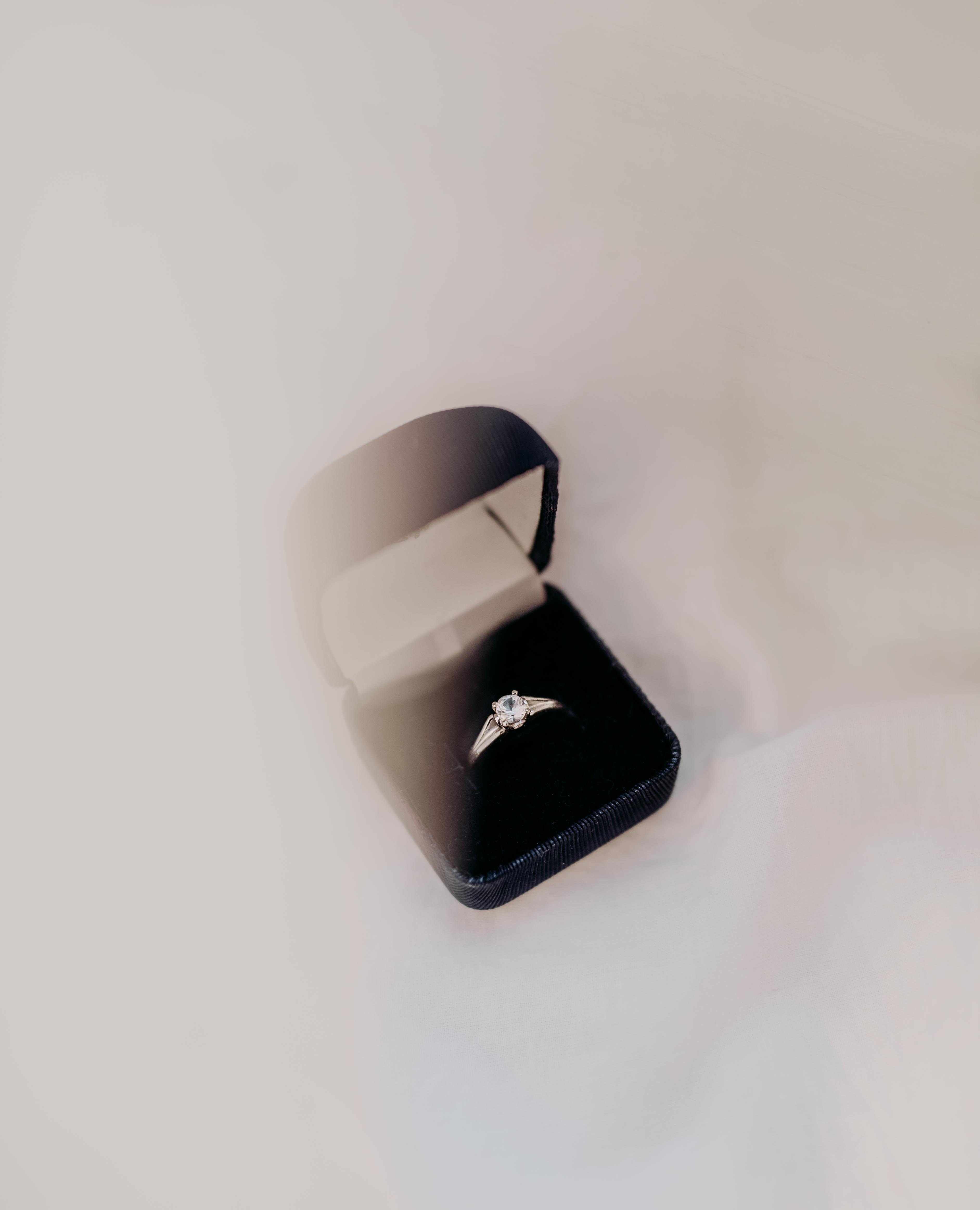 silver engagement ring on black box