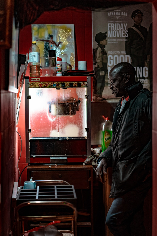 man standing beside popcorn maker