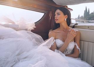 woman wearing white sweetheart-neckline wedding dress inside vehicle
