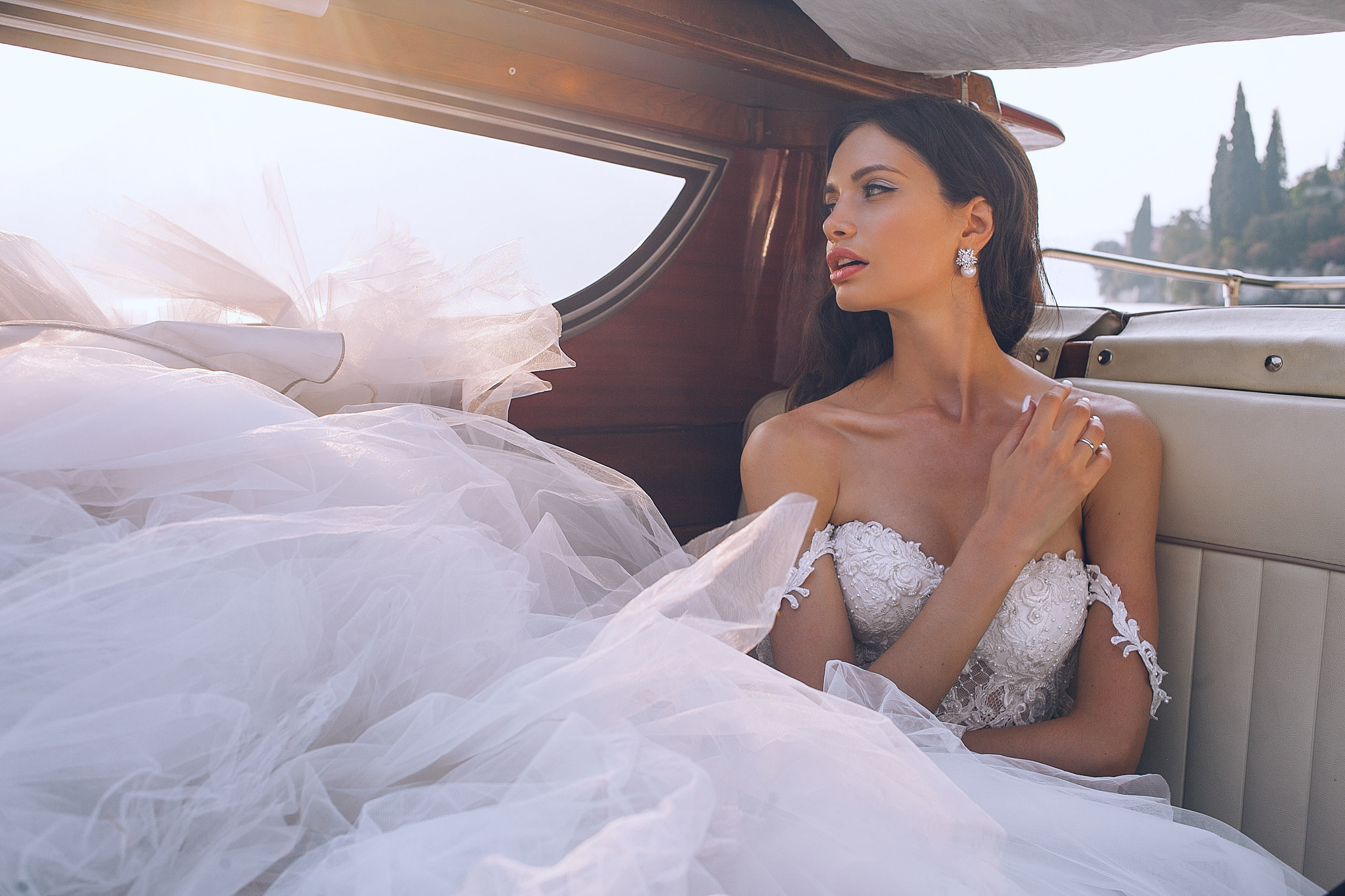 woman wearing white sweetheart-neckline wedding dress inside vehicle