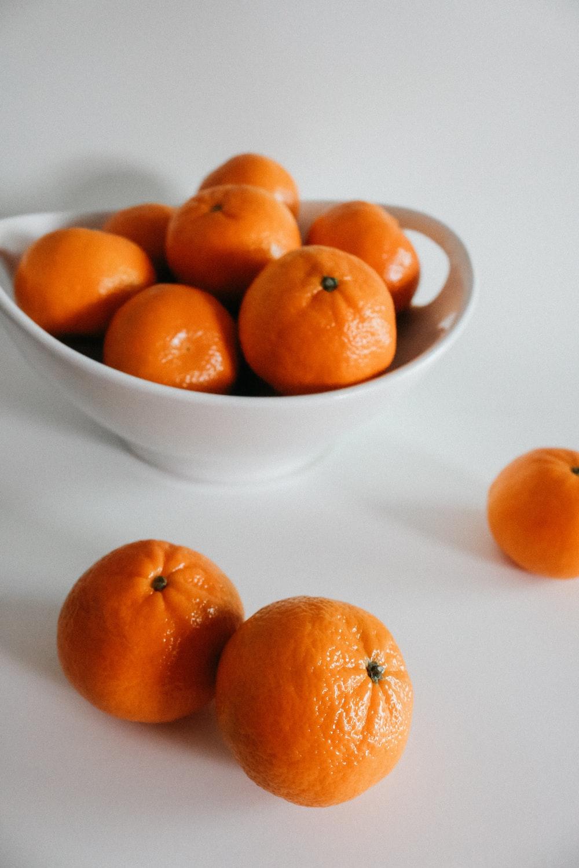 orange fruits on white bowl