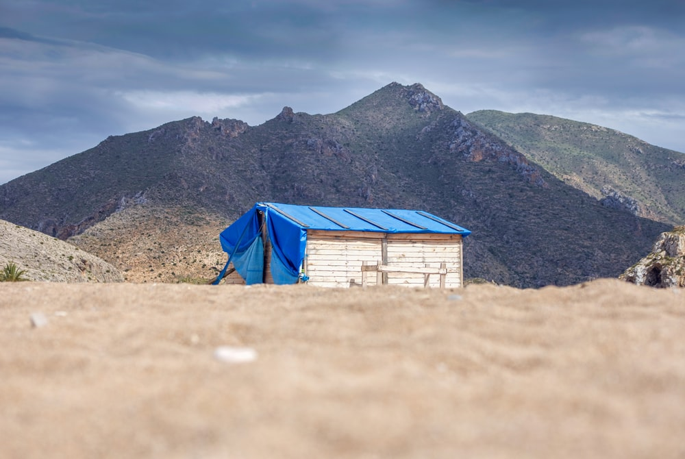 brown wooden shed with blue tarp roof beside mountain during daytime