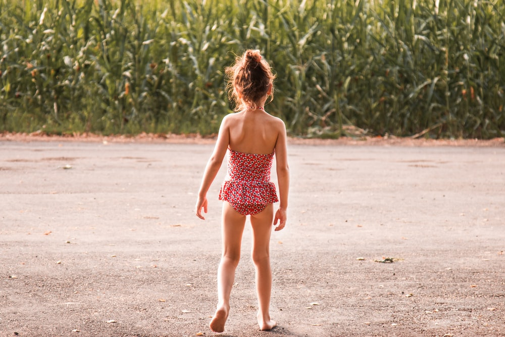 girl wearing onepiece standing beside corn plant during daytime