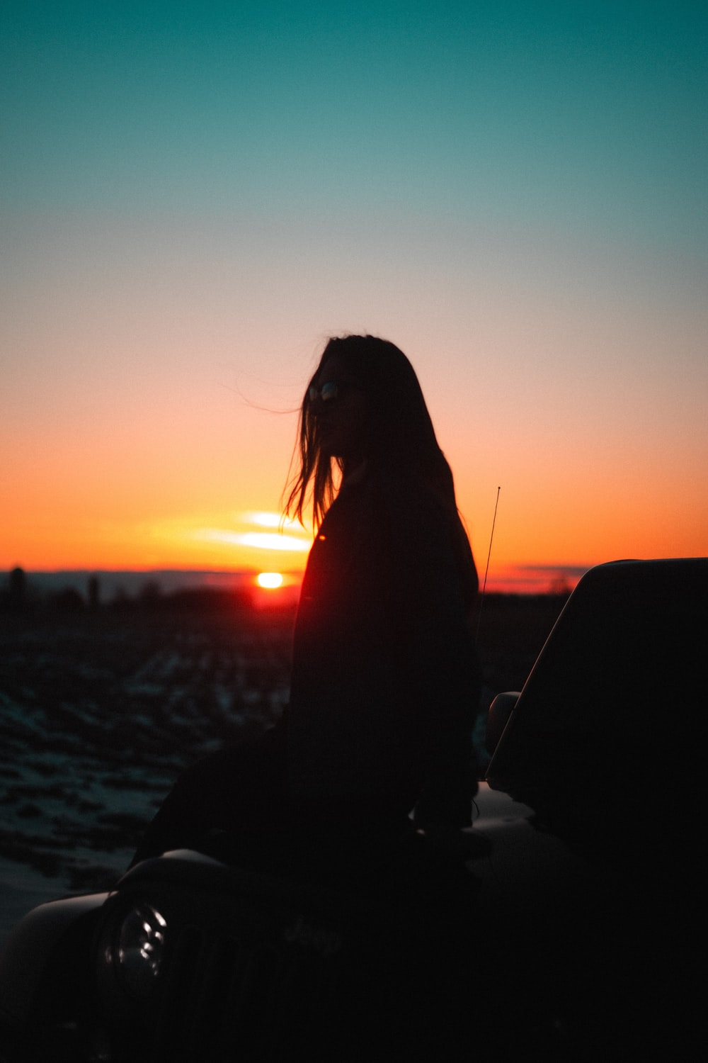 silhouette of girl sitting during golden hour