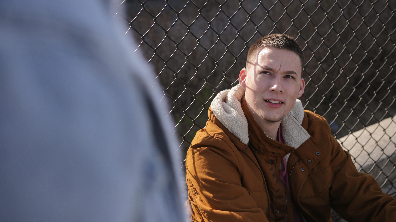 man wearing brown jacket sitting near gray link fence