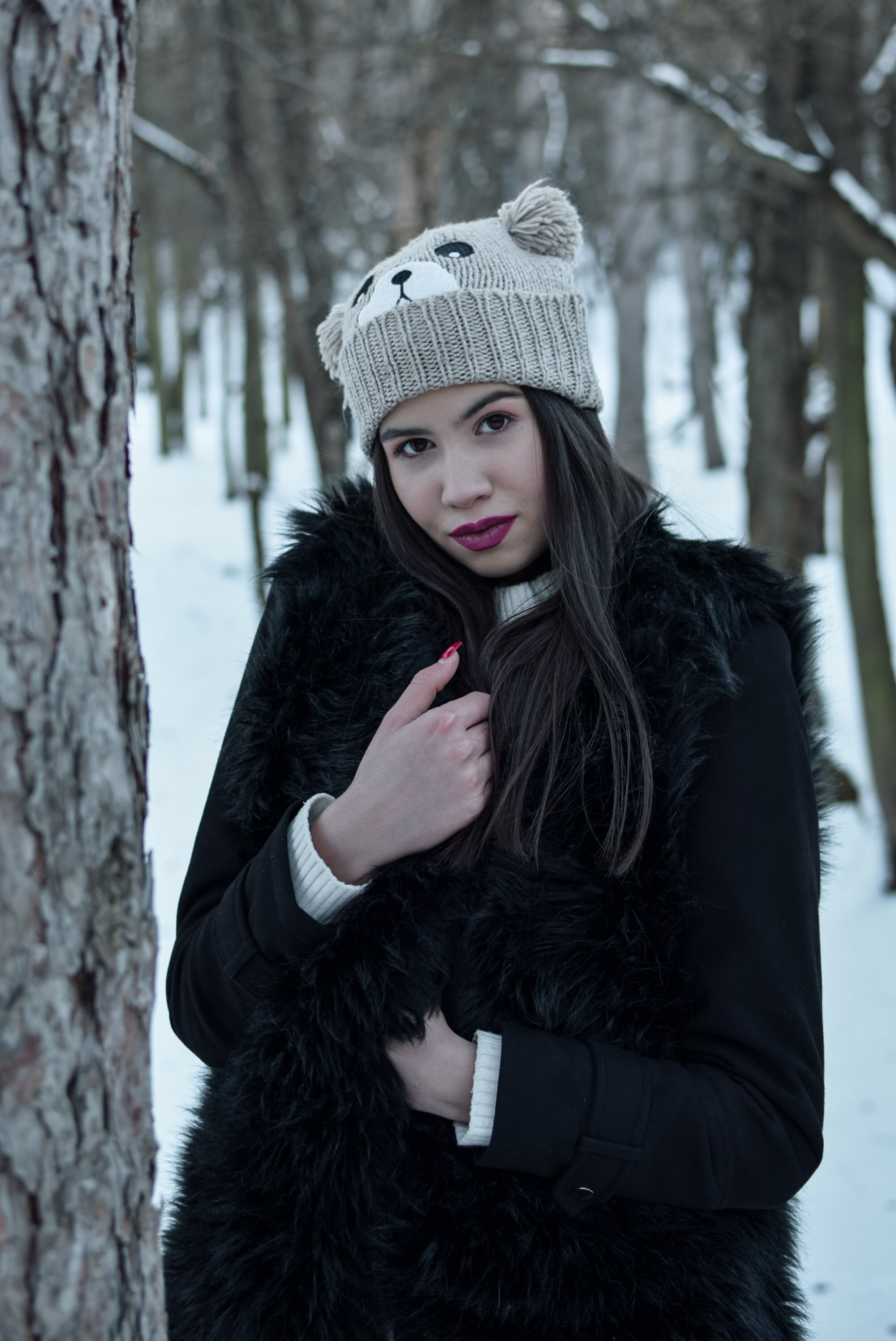 woman wearing black coat and gray bear knit cap standing beside tree