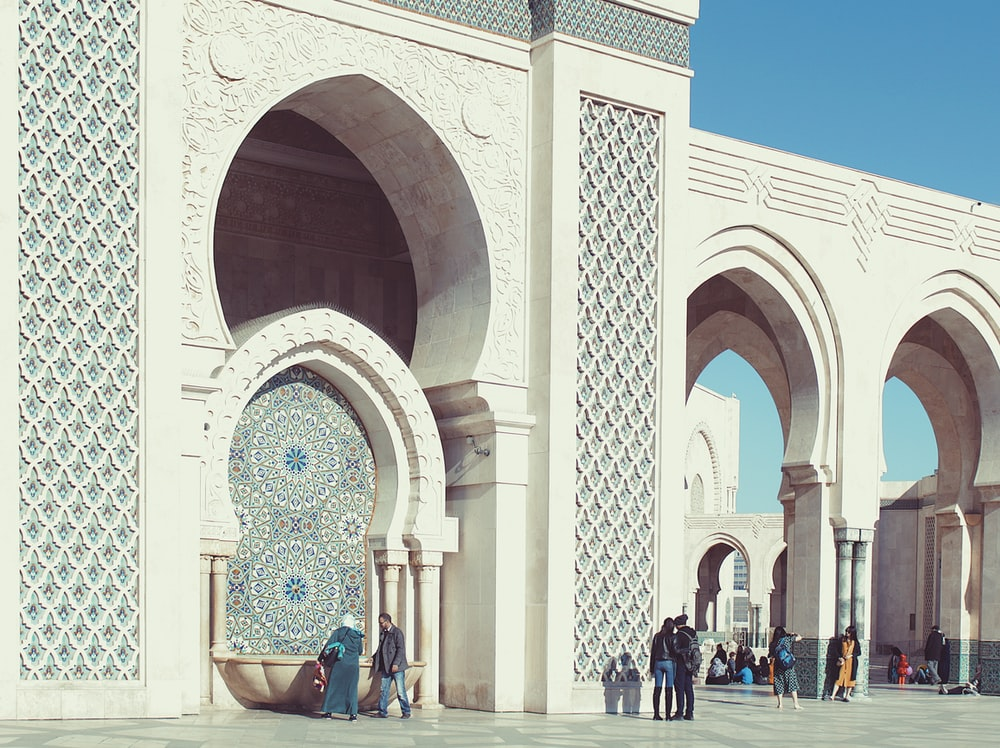 people walking beside triumphal arch
