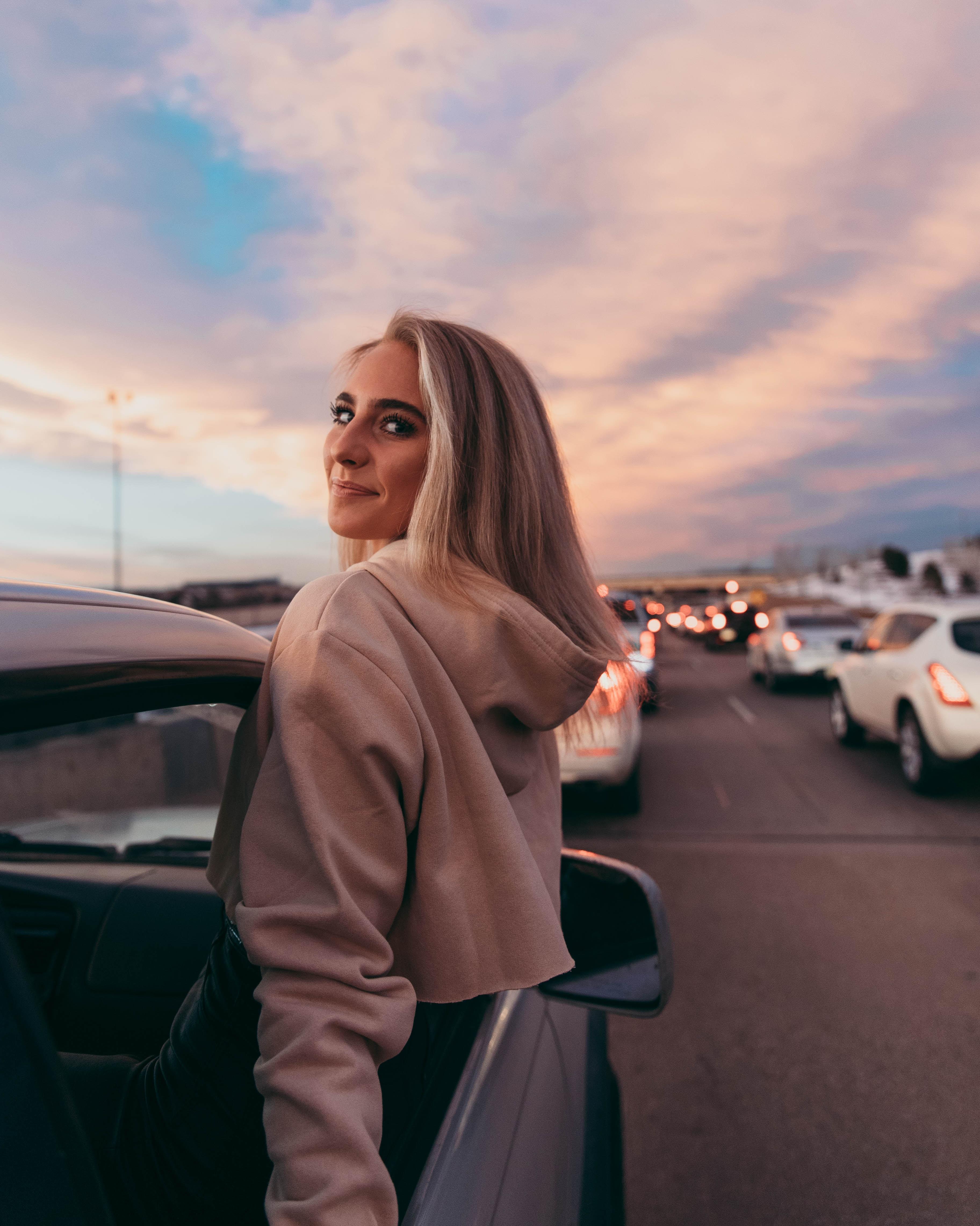 woman wearing beige pullover hoodie inside car during daytime
