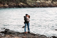 couple kissing on rock beside sea during daytime