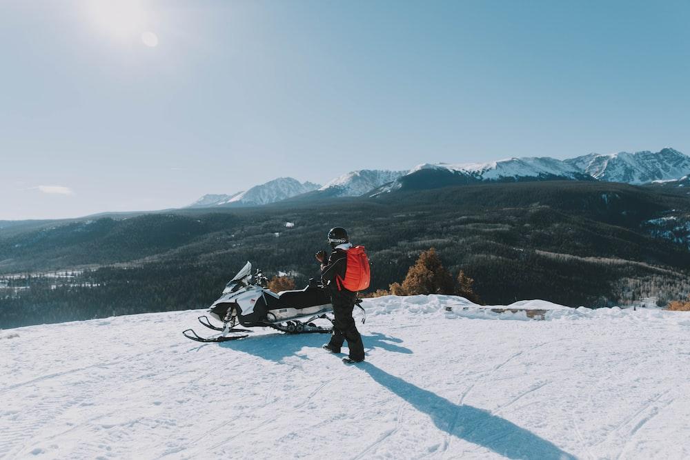 man walking near the white and black snowmobile