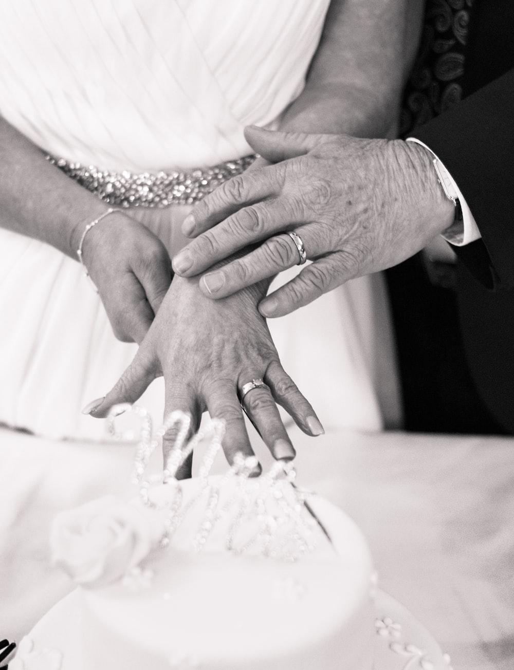 grayscale photography of wedding couple hands