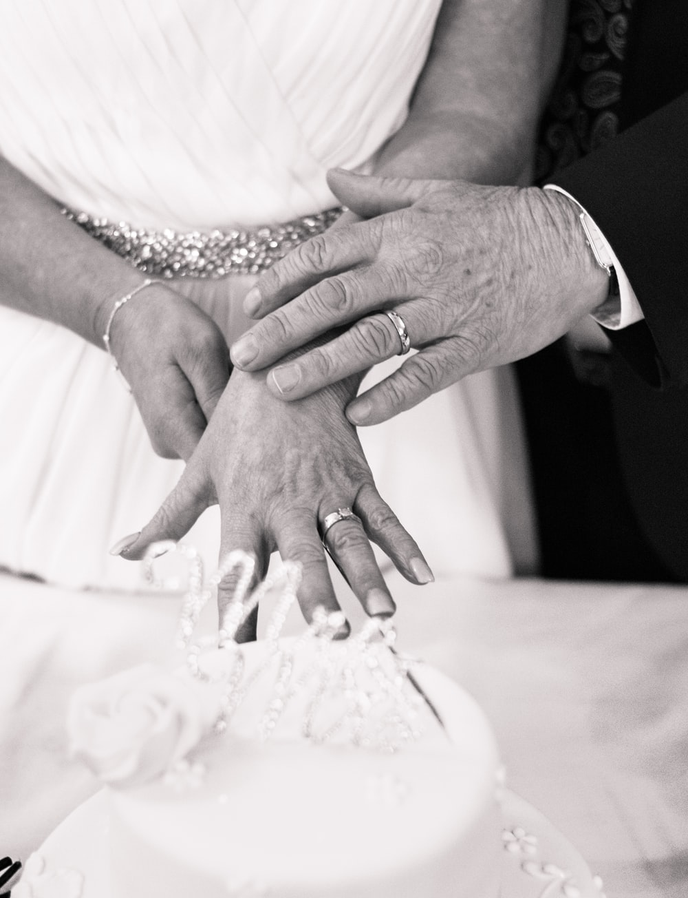 grayscale photography of wedding couple hands