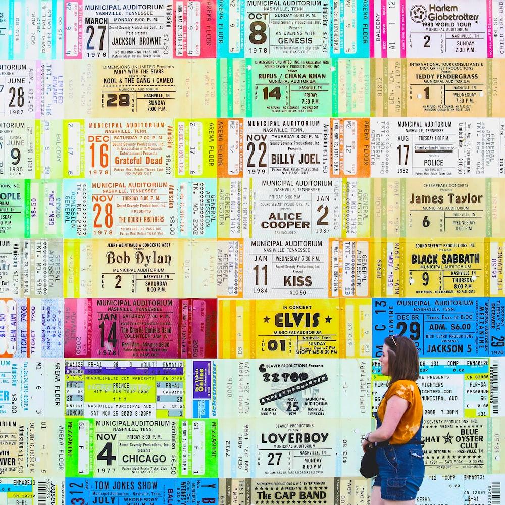 woman in blue jumpshorts beside assorted-ticket wall graffiti