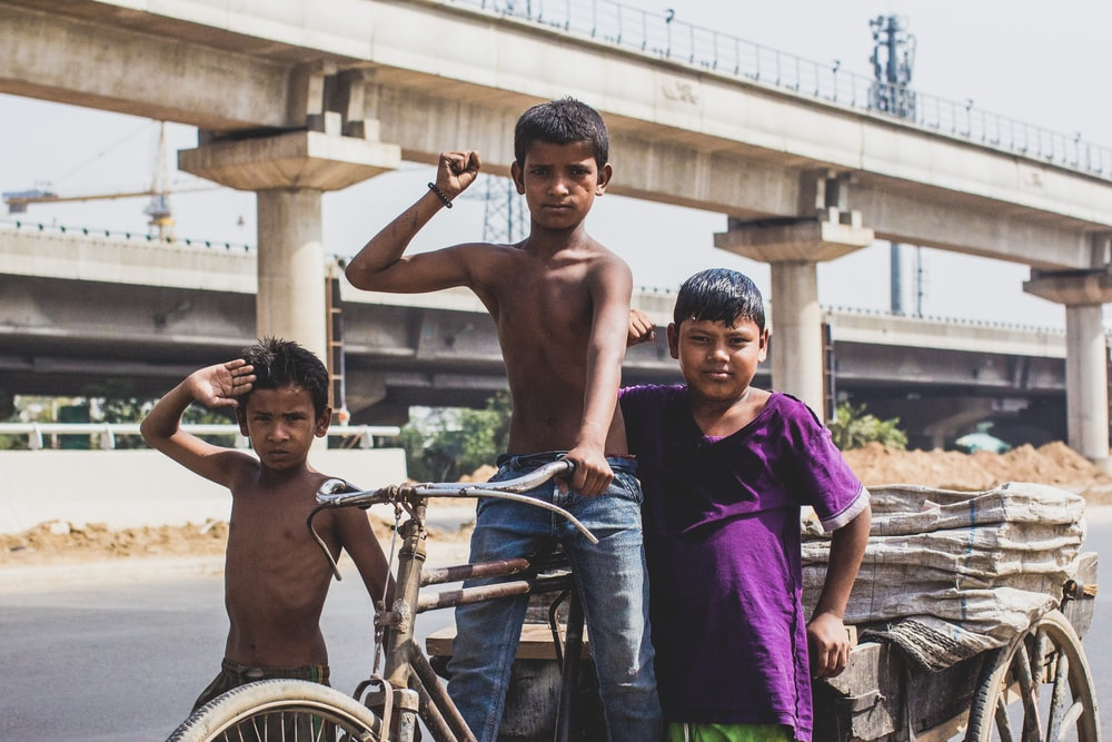 three boy raising right hands while riding on trike