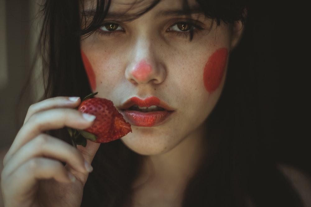 woman holding strawberry fruit