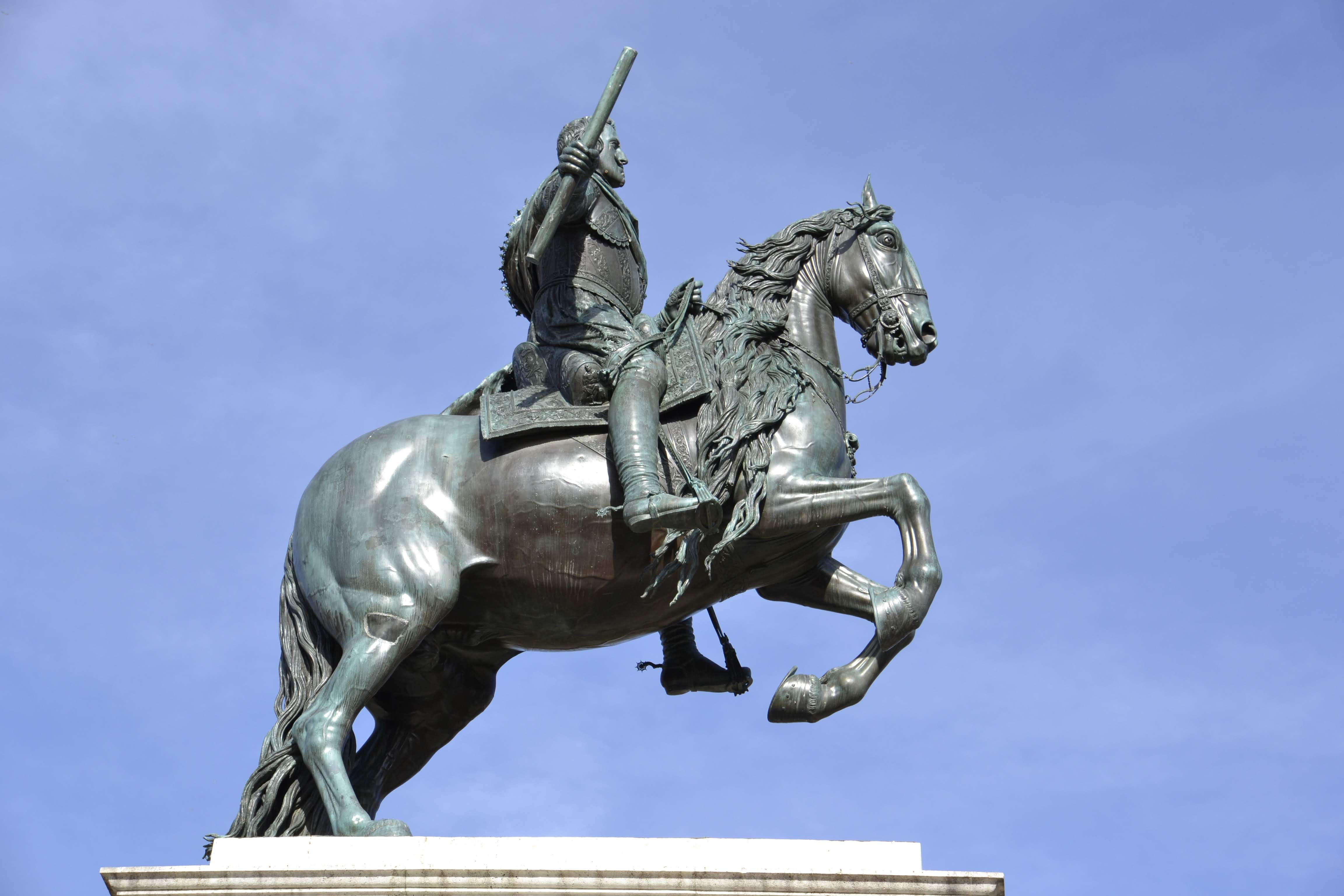man riding on horse statue under blue sky