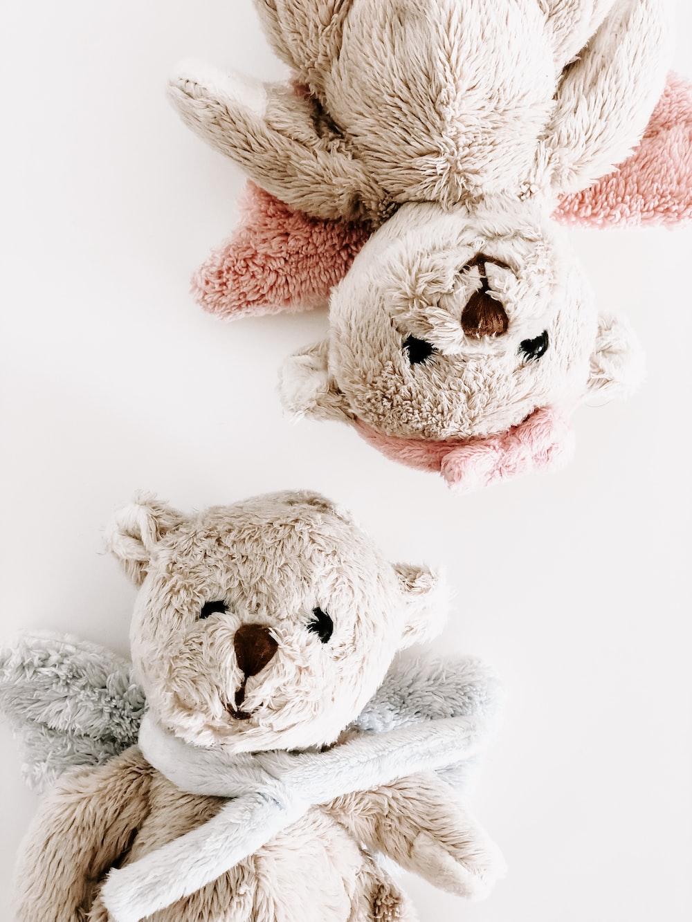 two brown bear plush toys on white surface