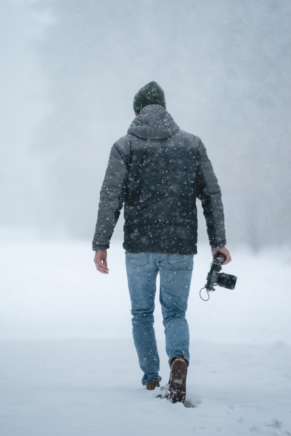 man in gray jacket holding camera while walking on snow