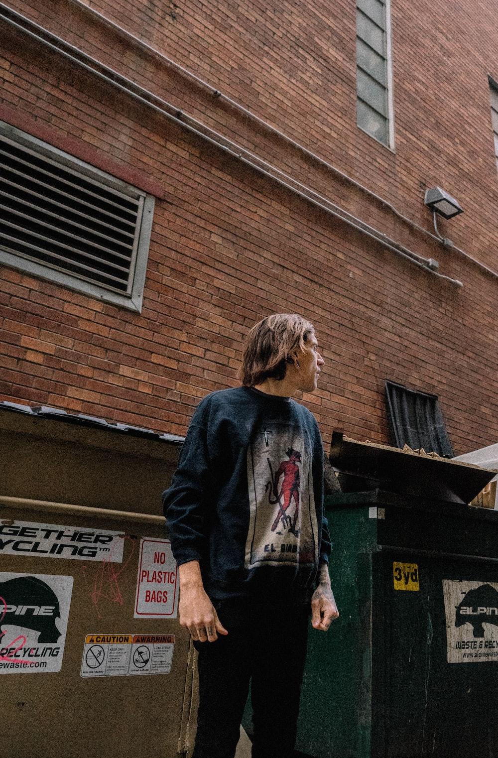 man standing beside building and trash bin
