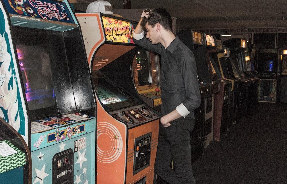 man standing in front of arcade machine