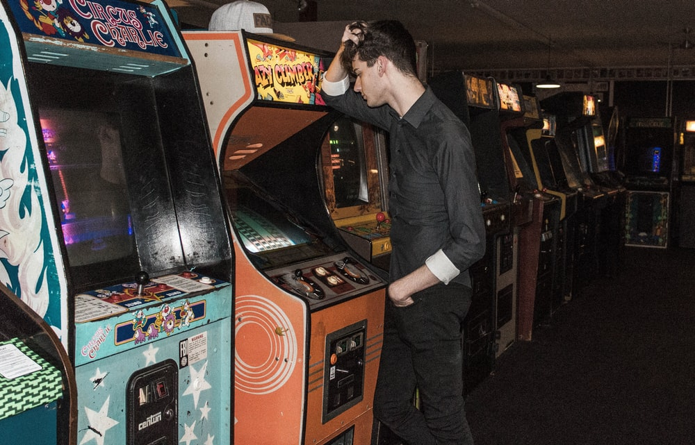 man standing in front of arcade machine