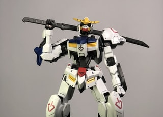 white, blue, and yellow robot holding sword toy on black panel
