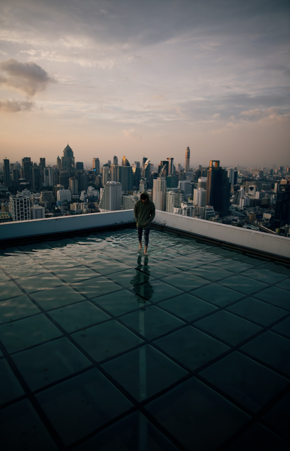 man standing on top of building facing high-rise building under gray sky