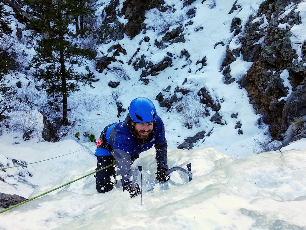 man climbing on snow mountain
