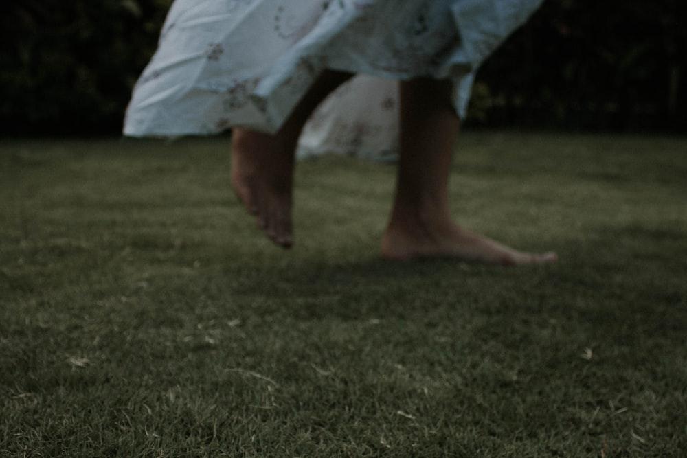person wearing white dress walk in lawn