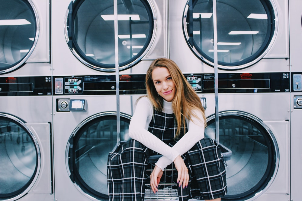 woman sitting on metal in front of laundry machines