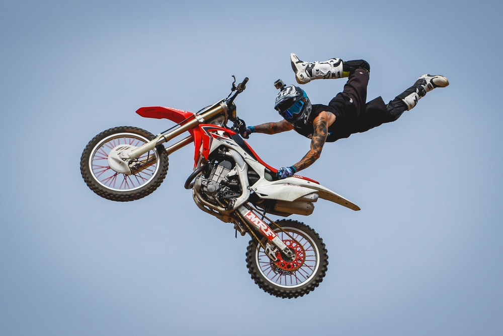 male rider with arm tattoos riding dirt bike doing trick on mid air during daytime
