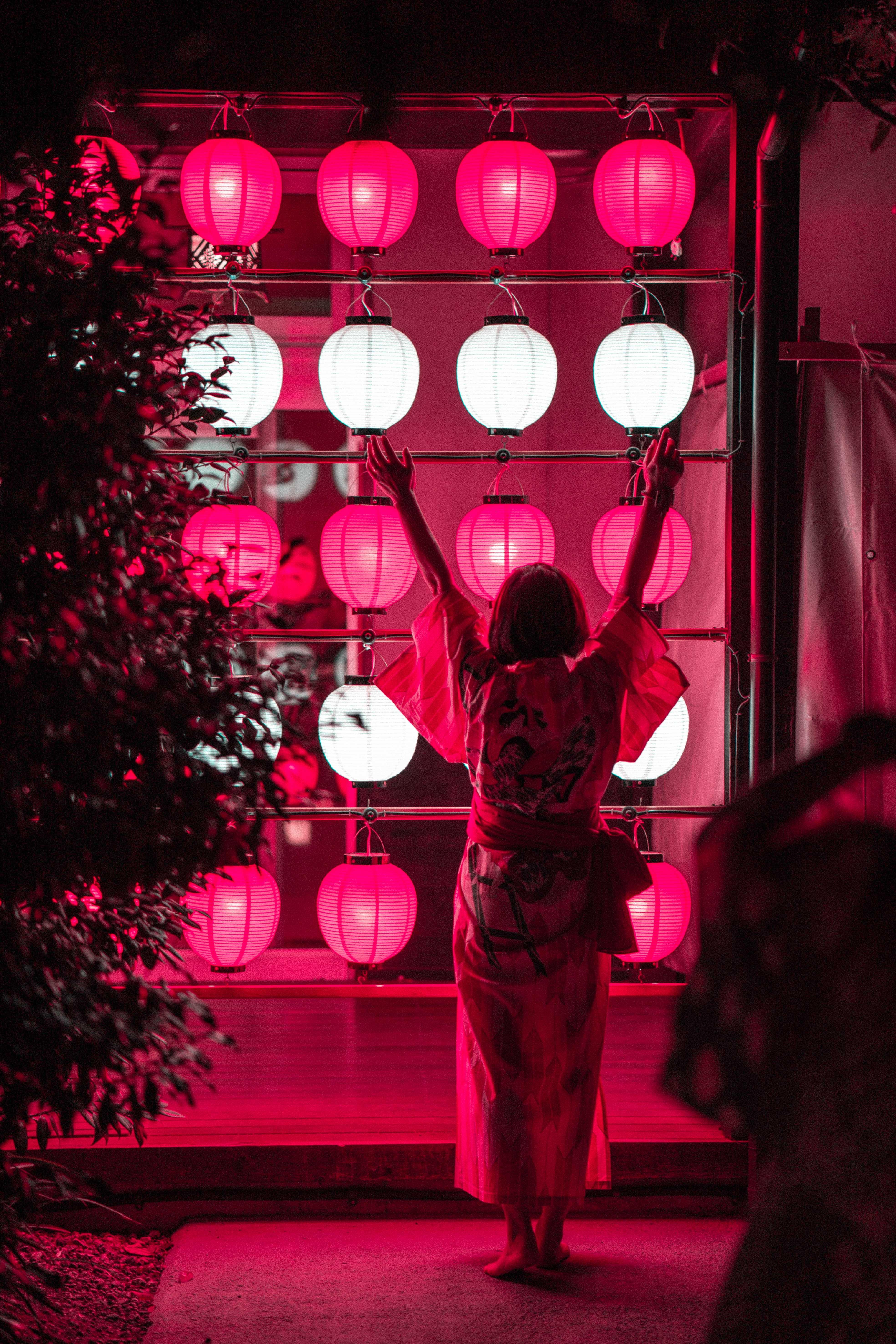 woman facing pink and white lantern
