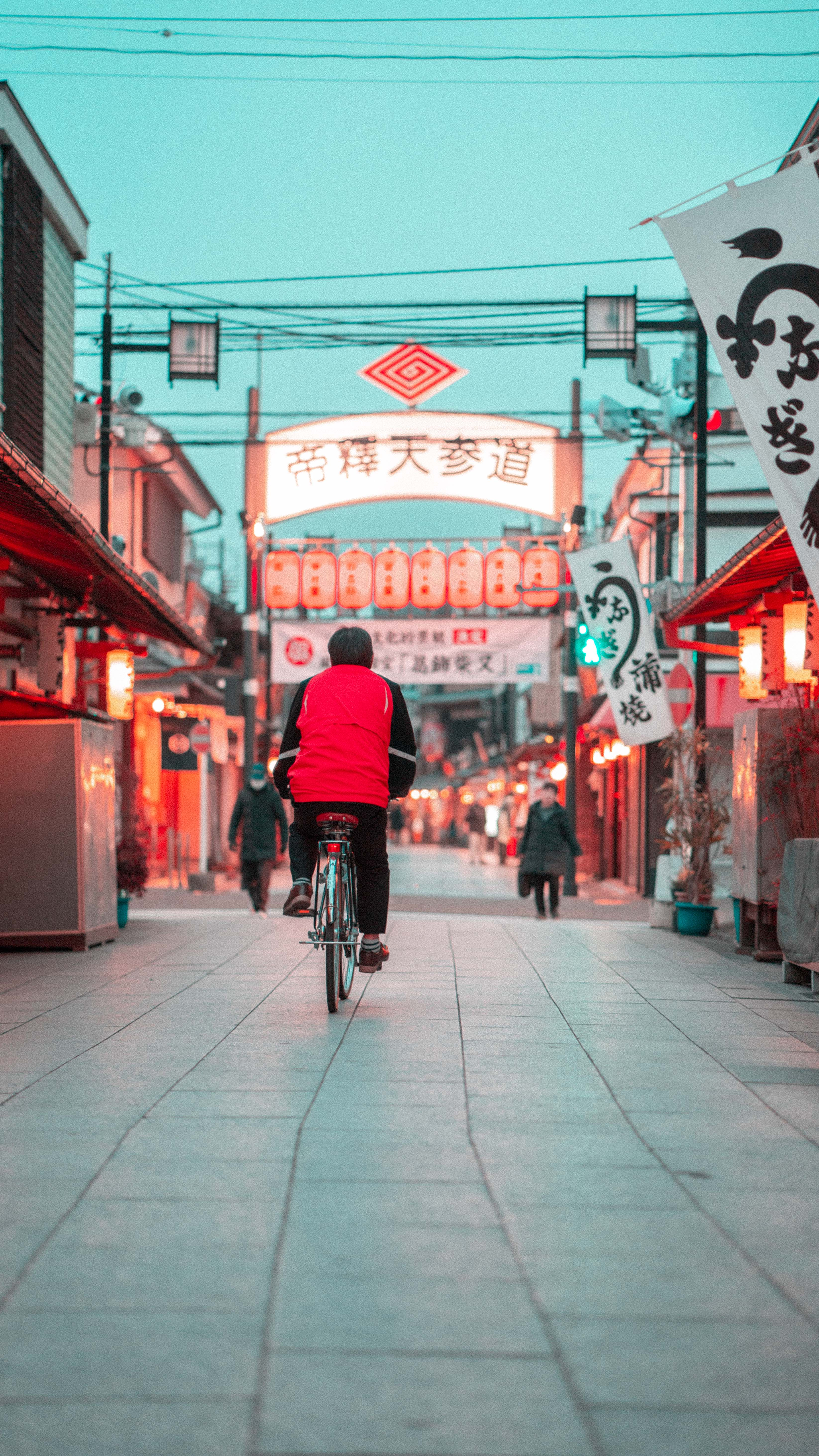 person cycling on streets with Kanji signs during daytime